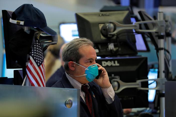 A trader wears a face mask on the floor of the New York Stock Exchange (NYSE) following traders testing positive for Coronavirus disease (COVID-19), in New York, U.S., March 19, 2020. (Photo: REUTERS/Lucas Jackson TPX IMAGES OF THE DAY)