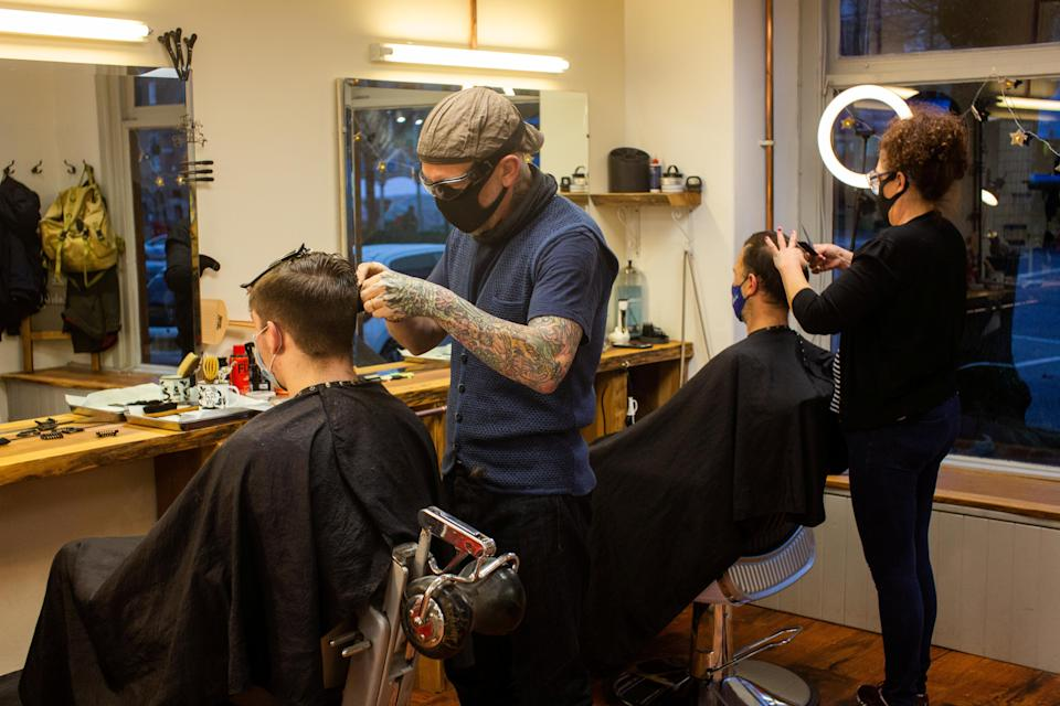Barbers Emma Rolfe and Toby Sewell from The Town Barber in Falmouth, Cornwall, get to work with two customers. (SWNS)
