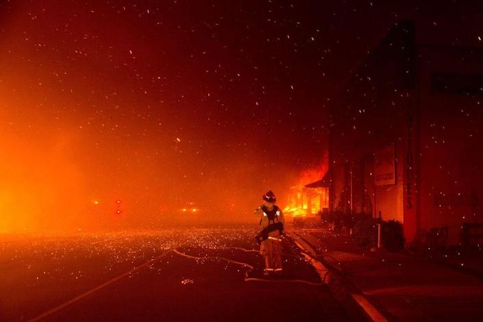 A fire fighter stands at the ready to protect a building across the street, as the Camp Fire burned out of control through Paradise, fueled by high winds in Butte County, Calif., on Nov. 8, 2018.