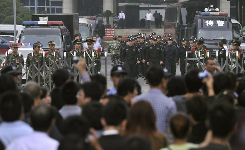 Security guards, paramilitary police and police officers stand guard as people gather for a rally in front of the city government office building in Zhejiang province's Ningbo city, China, Saturday, Oct. 27, 2012. Thousands of people in the eastern Chinese city clashed with police while protesting the proposed expansion of a petrochemical factory that they say would spew pollution and damage public health, townspeople said. (AP Photo/Kyodo News) JAPAN OUT, MANDATORY CREDIT, NO LICENSING IN CHINA, FRANCE, HONG KONG, JAPAN AND SOUTH KOREA