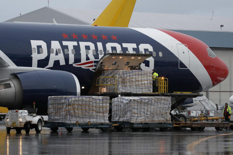 Palettes of N95 respirator masks are off-loaded from the New England Patriots football team's customized Boeing 767 jet on the tarmac, Thursday, April 2, 2020, at Logan Airport in Boston, after returning from China. The Kraft family deployed the Patriots team plane to China to fetch more than one million masks for use by front-line health care workers to prevent the spread of the coronavirus. (AP Photo/Elise Amendola)