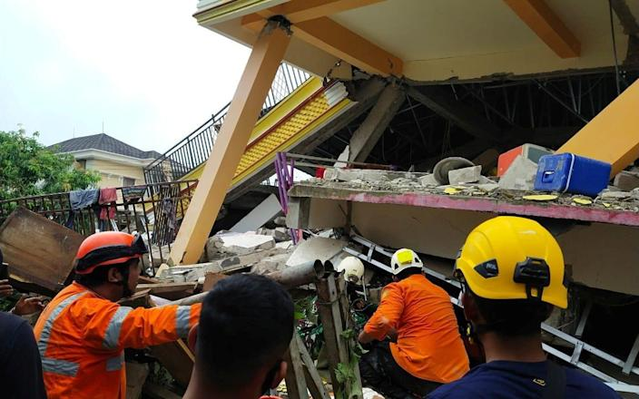 Members of a search and rescue agency team dig through rubble after an earthquake, in Mamuju - Reuters