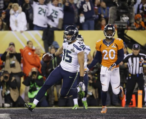 Seattle Seahawks' Jermaine Kearse (15) scores on a 23-yard touchdown reception in front of Denver Broncos' Mike Adams (20) during the second half of the NFL Super Bowl XLVIII football game Sunday, Feb. 2, 2014, in East Rutherford, N.J. (AP Photo/Matt Slocum)