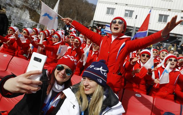<p>Fans take a selfie in front of North Korean cheerleaders holding unification flags. REUTERS/Kai Pfaffenbach </p>