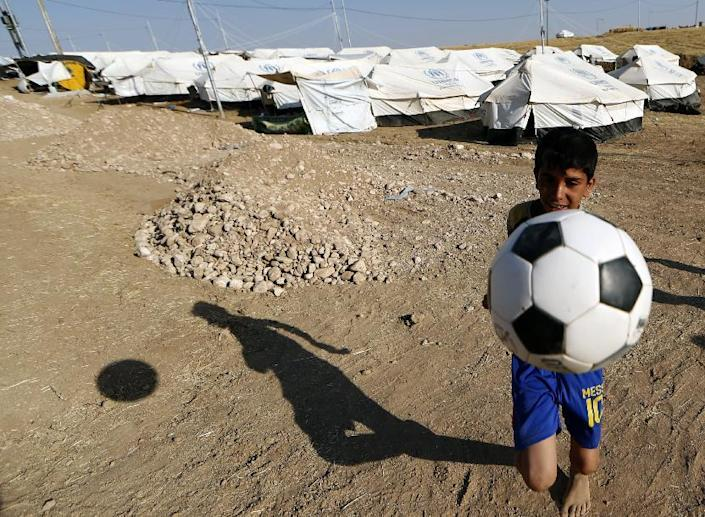 A boy plays with a ball at a camp for displaced Iraqi Shiite Turkmen in Shikhan, in Kurdistan's Dohuk province, on June 24, 2014 (AFP Photo/Karim Sahib)