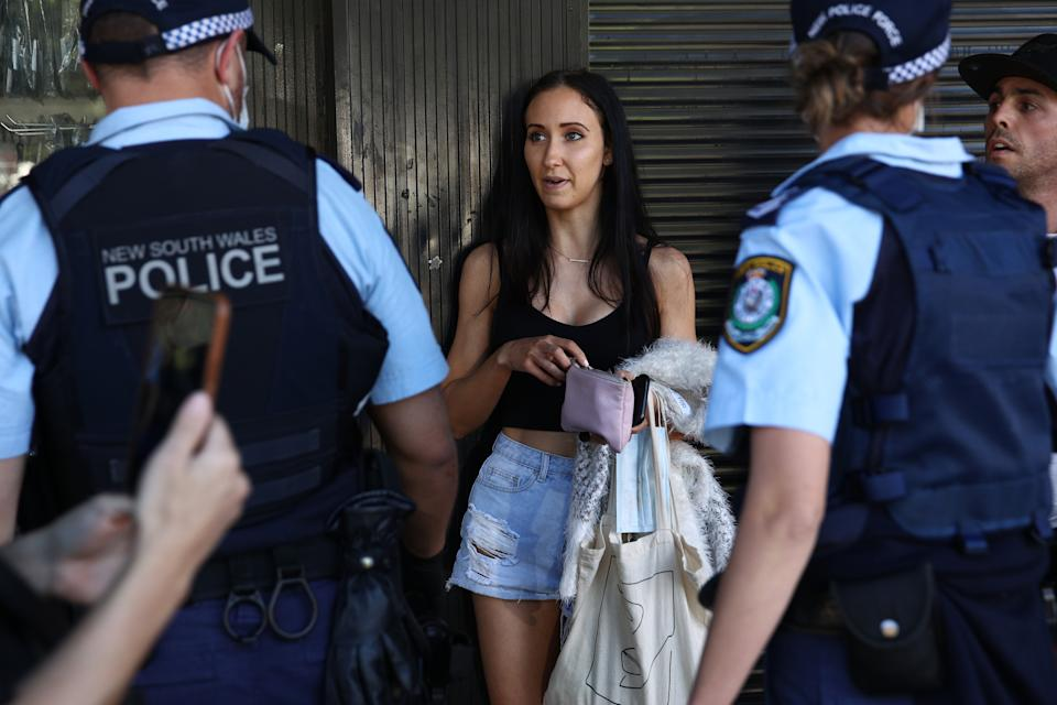 A woman is questioned by NSW Police on Broadway on Saturday during anti-lockdown protests. Source: Getty