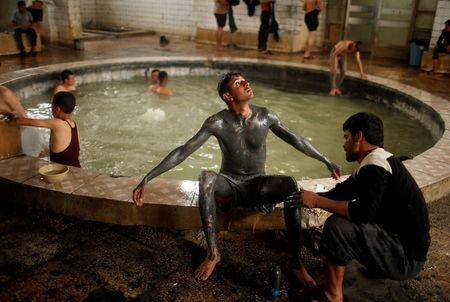 An Iraqi cover his boy with sand from a sulfur pond at Hammam al-Alil city south of Mosul