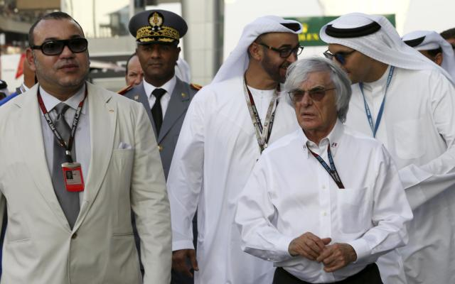 King of Morocco Mohammed VI, left is flanked by Formula One chief executive Bernie Ecclestone as they arrive to attend the Abu Dhabi Formula One Grand Prix at the Yas Marina racetrack in Abu Dhabi, United Arab Emirates, Sunday, Nov. 3, 2013. (AP Photo/Luca Bruno)