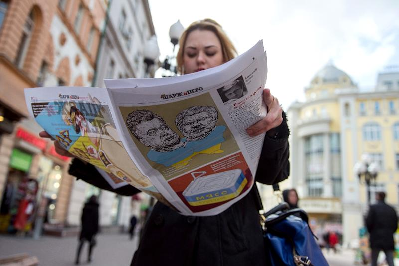 A woman looks through her copy of the first issue of satirical weekly magazine Sharzh i Pero as she walks along a street in central Moscow on April 21, 2015 (AFP Photo/Dmitry Serebryakov)
