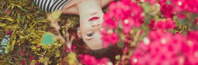 A woman lying in a bed of brightly colored flowers, looking up