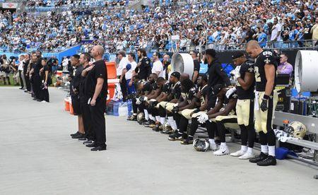 Sep 24, 2017; Charlotte, NC, USA; New Orleans Saints players stand and sit during the national anthem at Bank of America Stadium. Mandatory Credit: Bob Donnan-USA TODAY Sports