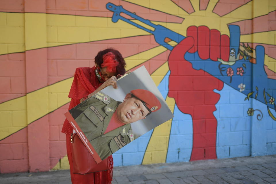 """A government supporter known as """"Caperucita,"""" or Little Red Riding Hood, holds a photo of late Venezuelan President Hugo Chavez as she looks for something in her purse in Plaza Bolivar, near the National Assembly where newly elected National Assembly lawmakers will be sworn-in and hold their first session of the year in Caracas, Venezuela, Tuesday, Jan. 5, 2021. (AP Photo/Matias Delacroix)"""