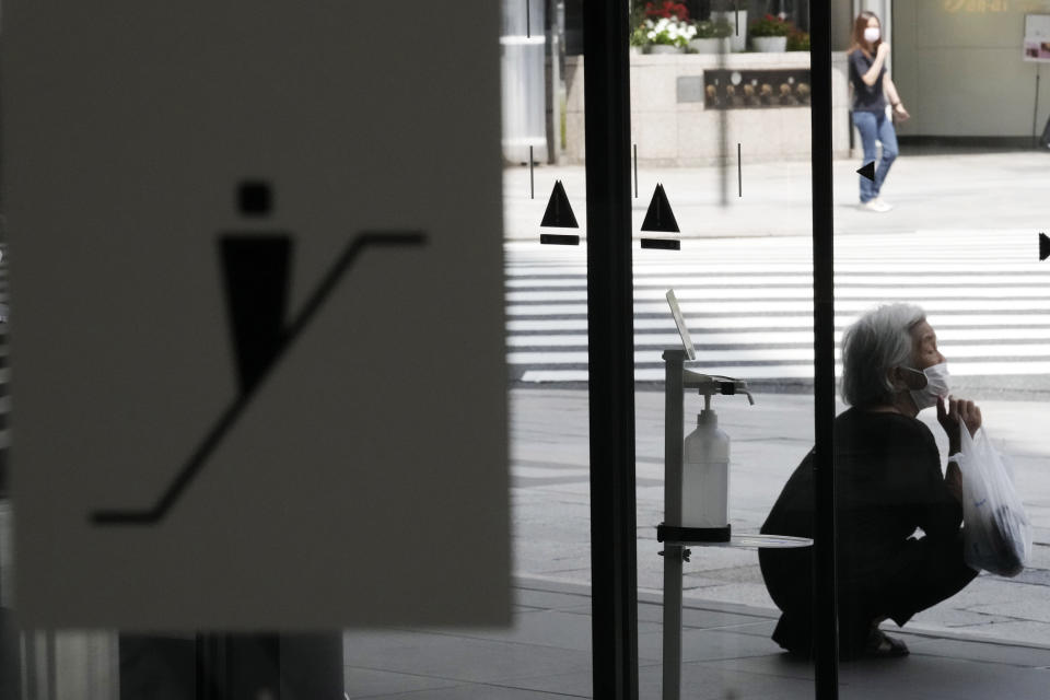 A woman wearing a protective mask to help curb the spread of the coronavirus takes shelter in the shade from high temperature Thursday, July 29, 2021, in Tokyo. (AP Photo/Eugene Hoshiko)