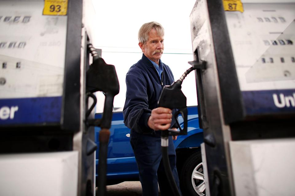 In this Tuesday, March 26, 2019 photo, Eddie Cartwright finishes gassing up a pick-up in South Mills, N.C. Gas stations have evolved dramatically since the country's first drive-in service station opened in Pennsylvania in 1913, according to the Smithsonian Institution. For most, the decline in service was all about economics. Let people pump their own gas, except in New Jersey, the only state that won't allow it and get their car serviced somewhere else. (Stephen M. Katz/The Virginian-Pilot via AP)