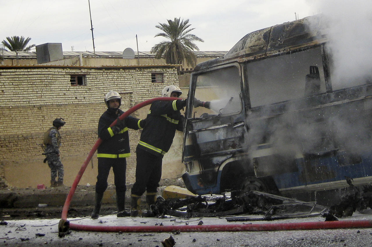 Iraqi firefighters try to extinguish a burning bus at the scene of a car bomb explosion in Karradah in downtown Baghdad, Iraq, Thursday, Feb. 23, 2012. A swift series of bombings and shootings killed dozens of people across the Iraqi capital early Thursday in attacks that mostly appeared to target police, officials said. (AP Photo/Hadi Mizban)