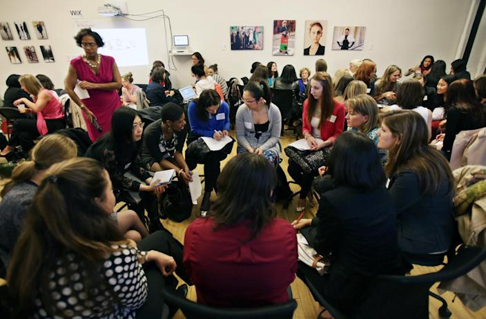 """This April 16, 2013 photo provided by Wix Lounge shows group facilitator Franne McNeal, standing left,directing women attending a """"lean in"""" circle in New York. The group is inspired by Facebook COO Sheryl Sandberg's book """"Lean In"""" which seeks to empower women in the workplace. (AP Photo/Wix Lounge, Galo Delgado)"""