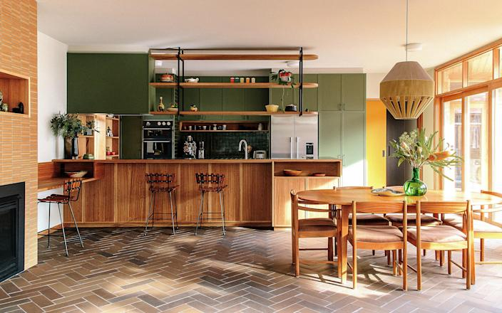 """AFTER: """"I really love the kitchen, it's just such a pleasure to work in as it's so gorgeous,"""" Claire says. """"That room in particular is very calm. On a hot day it feels like you're in a cool lagoon, and on a cold day it's like you're in a warm cave—yet somehow it's always light!"""" Rounded blackbutt timber and aged bronze were used for the open shelving."""