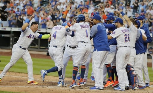 New York Mets' Wilmer Flores (4) is welcomed to home plate after hittting a walk-off home run during the tenth inning in the first game of a baseball doubleheader against the Philadelphia Phillies Monday, July 9, 2018, in New York. The Mets won 4-3. (AP Photo/Frank Franklin II)