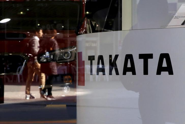 A logo of Takata Corp is seen with its display as people are reflected in a window at a showroom for vehicles in Tokyo