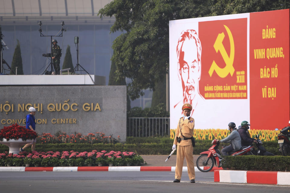 A police officer directs traffic in front of the National Convention Center in Hanoi, Vietnam, Saturday, Jan. 23, 2021. Almost 1,600 leading members of Vietnam's Communist Party on Tuesday begin a meeting to set policy for the next five years and select the group's senior members to steer the nation. (AP Photo/Hau Dinh)