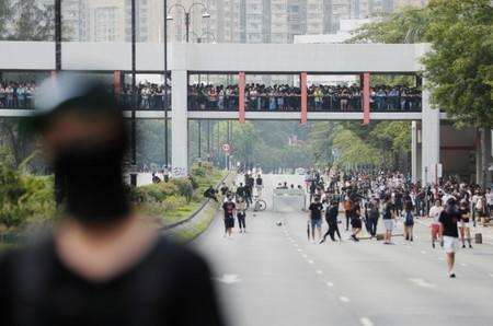 Anti-government protesters walk on the street while people watch from a bridge during a protest in Tai Po district, in Hong Kong
