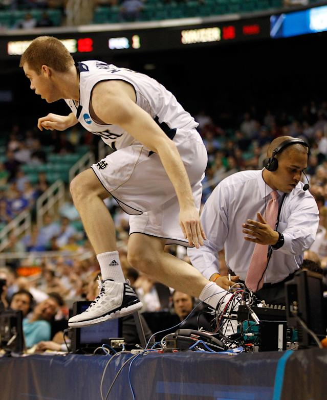 GREENSBORO, NC - MARCH 16: Scott Martin #14 of the Notre Dame Fighting Irish leaps over the table after running after a loose ball in the first half against the Xavier Musketeers during the second round of the 2012 NCAA Men's Basketball Tournament at Greensboro Coliseum on March 16, 2012 in Greensboro, North Carolina. (Photo by Streeter Lecka/Getty Images)