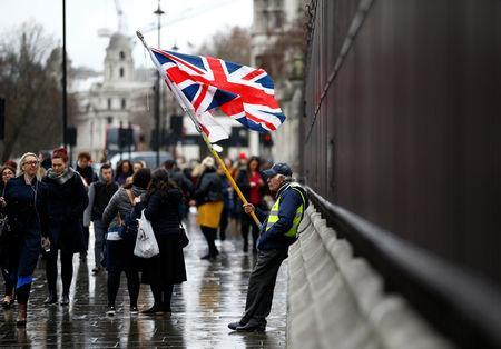 People walk past a pro-Brexit protester outside the Houses of Parliament, after Prime Minister Theresa May's Brexit deal was rejected, in London, Britain, January 16, 2019. REUTERS/Henry Nicholls