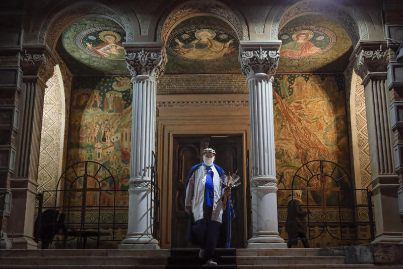An orthodox worshiper, wearing a mask for protection against the COVID-19 virus, exits the church after a religious service in the Black Sea port of Constanta, Romania, late Tuesday, May 26, 2020. (AP Photo/Vadim Ghirda)