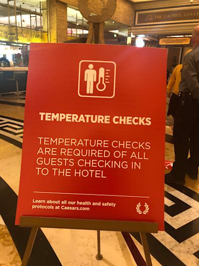 A sign in the lobby of Caesars Palace in Las Vegas announces the hotel's new temperature check policy.