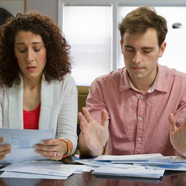 Couple-looking-worried-as-they-pay-bills_web