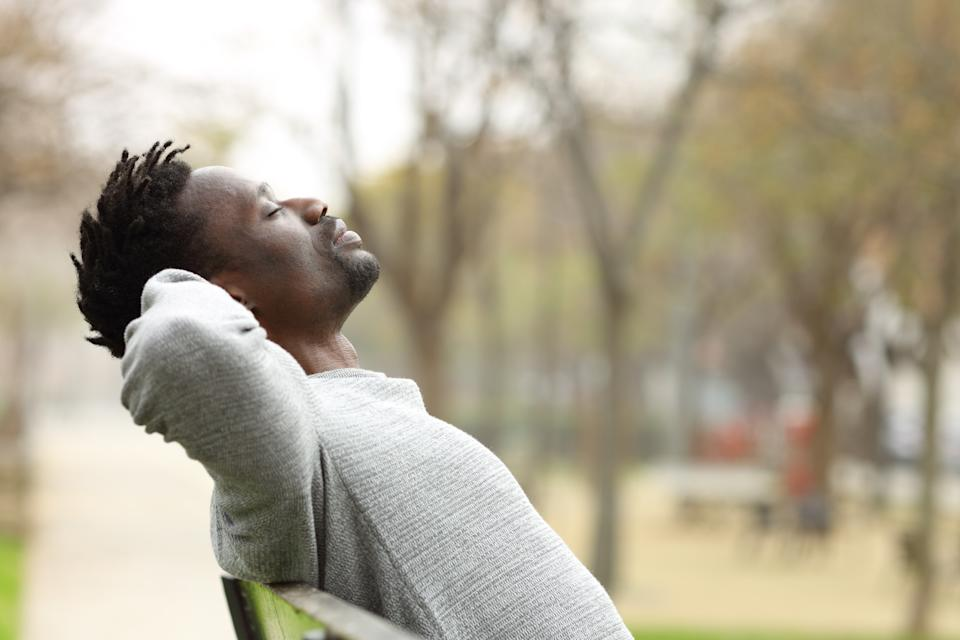 Side view portrait of a black man relaxing sitting on a bench in a park