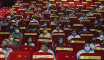 People wait to get inoculated against COVID-19 at a cinema hall in Mumbai, India, Tuesday, Aug. 17, 2021. (AP Photo/Rafiq Maqbool)