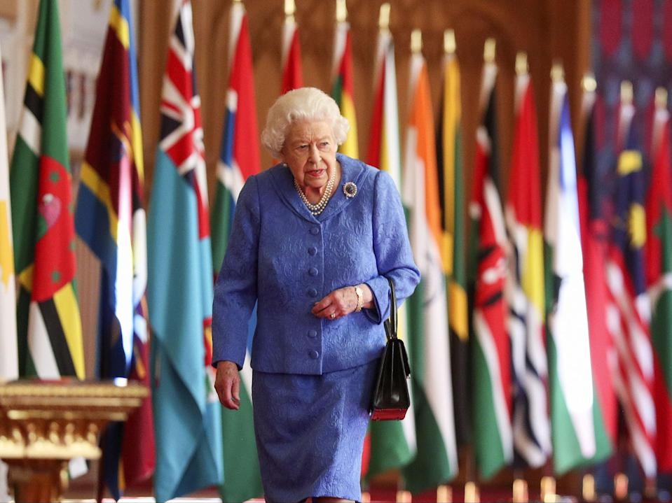 Queen Elizabeth II walks past Commonwealth flags in St George's Hall at Windsor Castle , to mark Commonwealth DayPA