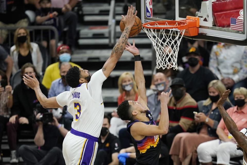 Los Angeles Lakers forward Anthony Davis, left, blocks the shot of Phoenix Suns guard Devin Booker, right, during the first half of Game 1 of their NBA basketball first-round playoff series Sunday, May 23, 2021, in Phoenix. (AP Photo/Ross D. Franklin)
