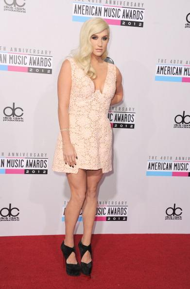 Ke$ha looks practically unrecognizable in a coy, pretty in pink lace dress and old Hollywood glamor hair.