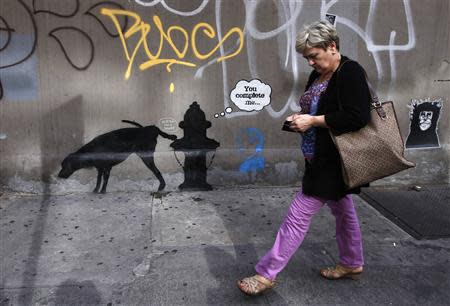A woman walks past a new work by British graffiti artist Bansky on West 24th street in New York City