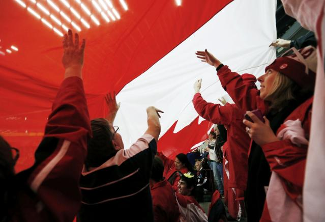 Canadian supporters pass a giant Canadian flag in the crowd as Canada plays Russia in their IIHF World Junior Championship ice hockey game in Malmo, Sweden, January 5, 2014. REUTERS/Alexander Demianchuk (SWEDEN - Tags: SPORT ICE HOCKEY)