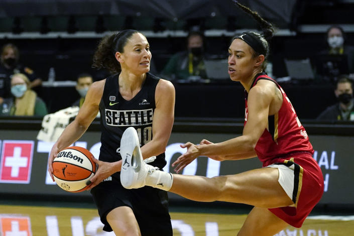 Seattle Storm's Sue Bird, left, looks for room to pass around Las Vegas Aces' Dearica Hamby in the second half of a WNBA basketball game Saturday, May 15, 2021, in Everett, Wash. (AP Photo/Elaine Thompson)
