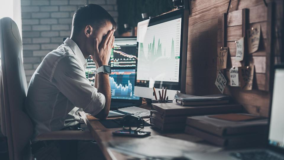 man upset with stock chart on computer screen