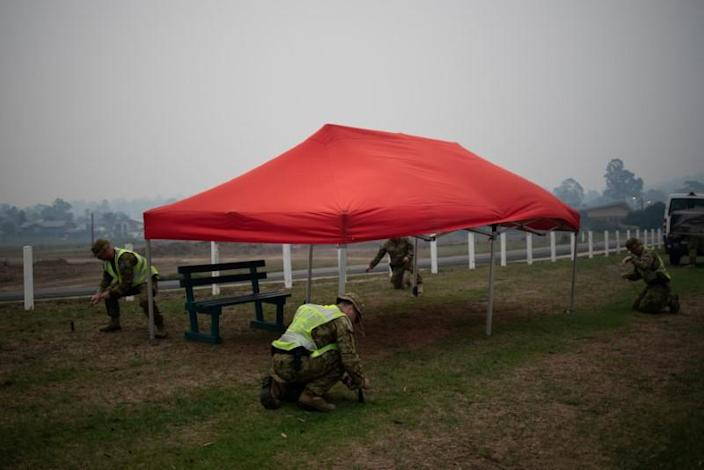 Members of a military support team support a tent from wind gusts, as smoke blankets the town of Eden