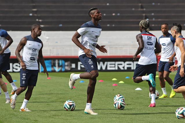 France's Paul Pogba, center, warms up during a training session at Santa Cruz stadium in Ribeirao Preto, Brazil, Saturday, June 28, 2014. France will face Nigeria on Monday in the round of 16 at the World Cup. (AP Photo/David Vincent)