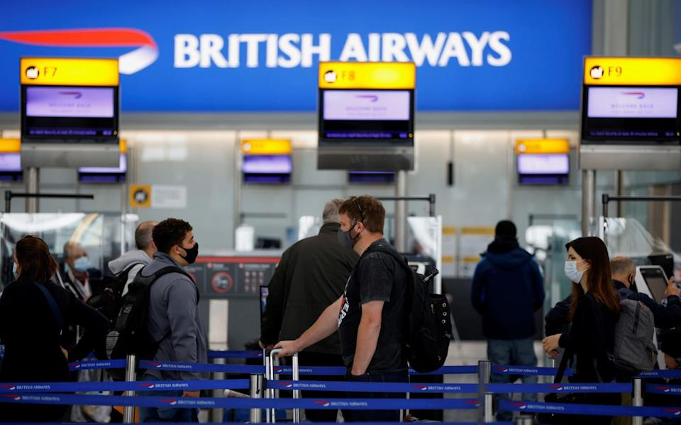 Passengers stand in a queue to the British Airways check-in desks at Heathrow Airport - JOHN SIBLEY/REUTERS