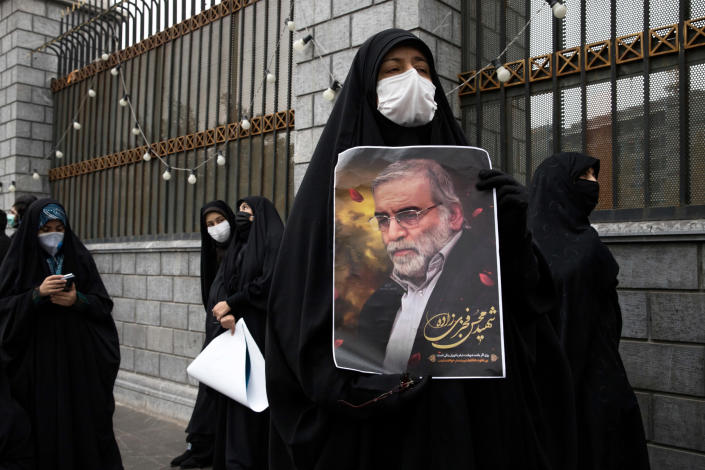 A protester holds an image of the Iranian nuclear scientist Mohsen Fakhrizadeh during a demonstration outside Parliament in Tehran on Saturday, Nov. 28, 2020, a day after Fakhrizadeh was killed. (Arash Khamooshi/The New York Times)