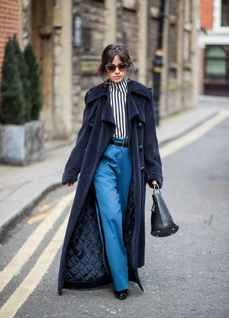 <p>Vertical stripes, high rise trousers, and a floor-grazing trench give the illusion of legs for days. The velvety texture of Camila's coat pulls the entire look together. </p>