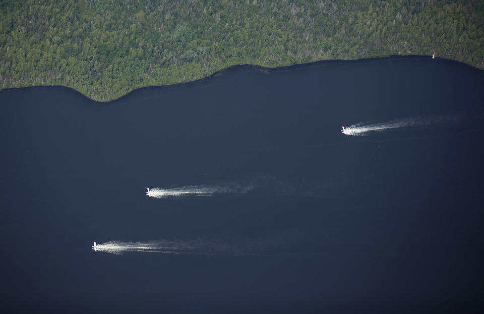 Aircrafts scoop up water from Sand Lake to drop onto the nearby Greenwood Fire, about 50 miles north of Duluth, Minn., Tuesday, Aug. 17, 2021, as seen from an airplane above the temporary flight restriction zone. (Alex Korman/Star Tribune via AP)