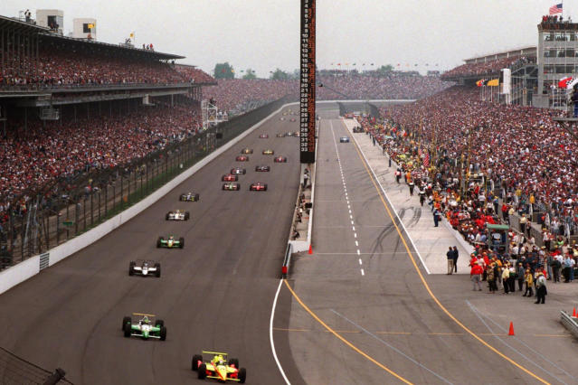 FILE - In this May 26, 1996 file photo, Tony Stewart leads Eliseo Salazar into the first turn during the 80th running of the Indianapolis 500 auto race at Indianapolis Motor Speedway. Indianapolis Motor Speedway and the IndyCar Series were sold to Penske Entertainment Corp. in a stunning move Monday, Nov. 4, 2019, that relinquishes control of the iconic speedway from the Hulman family after 74 years. (AP Photo/ Amy Sancetta, File)