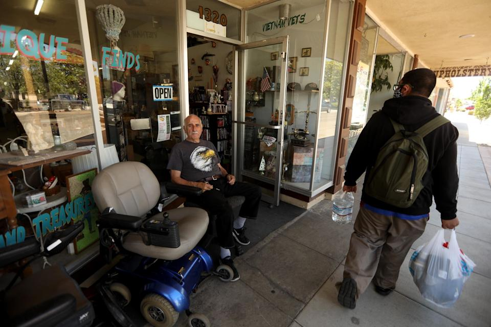 Larrie Long waits for customers in front of Thrift and Treasures in the historic downtown of Atwater