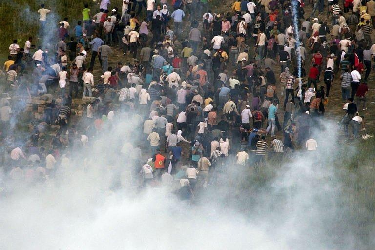 Demonstrators flee Israeli fired tear gas as they gather along Syria's border with Israel. Israeli troops opened fire on Sunday as protesters from Syria stormed a ceasefire line in the occupied Golan Heights, with Damascus saying 23 demonstrators were killed