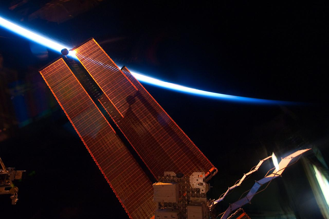 This image provided by NASA shows the intersecting thin line of Earth's atmosphere with the International Space Station's solar array wings photographed Thursday May 20, 2011 by an STS-134 crew member while space shuttle Endeavour remains docked with the station.