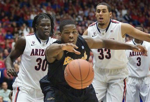 Long Beach State's Dan Jennings, center, reaches for the ball in front of Arizona's Angelo Chol (30) and Grant Jerrett (33) during the first half of an NCAA college basketball game in Tucson, Ariz., Monday, Nov. 19, 2012. (AP Photo/Wily Low)